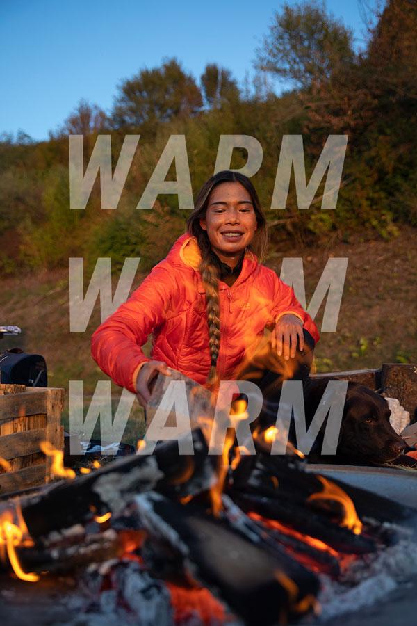 Kobieta przy ognisku z kurtką zimową